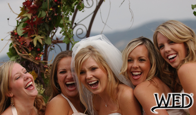 wedding reception bride laughing with her bridesmaids and Wedding Entertainment Director® logo