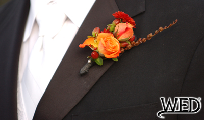 groom's wedding tuxedo lapel with floral boutonniere pinned on it and Wedding Entertainment Director® logo